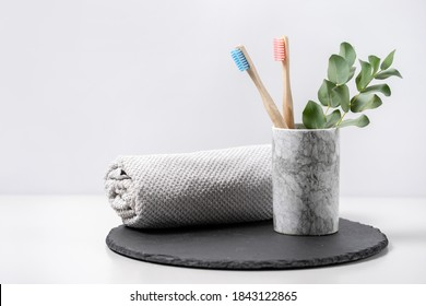 Concept of biodegradable objects. Two bamboo toothbrush in cup near bathroom towel and eucalyptus plant on black plate stand against white copy space background. Oral and dental care