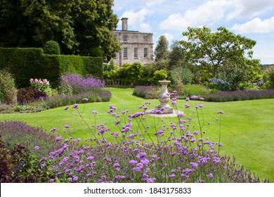 花のボーダーと生け垣、その他のガーデンファニチャーとデザインを備えた大規模な英国式ガーデンエステート