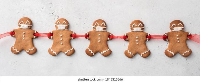 Quarantäne von Covid-19 zu Hause bleiben. Weihnachten Lebkuchenmänner mit einer Maske