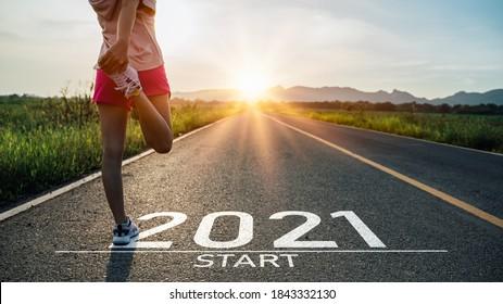 新年2021年またはストレートconceptを開始します。アスファルト道路に書かれた単語2021と日没時に新年の準備をしているアスリート女性ランナーストレッチ脚。挑戦またはキャリアパスと変化の概念。