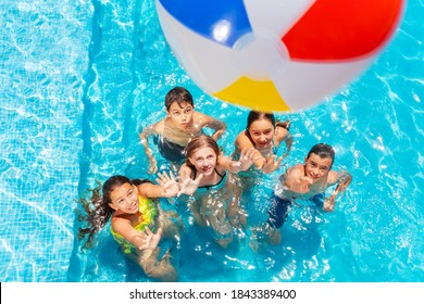Many kids in swimming pool play with inflatable ball view from above reaching hands up