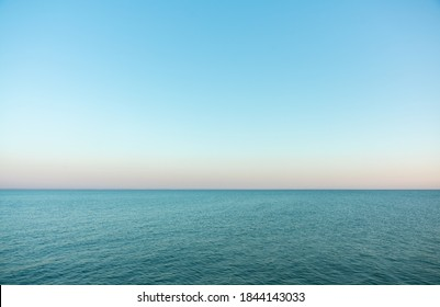 Ruhige abendliche Meeresoberfläche mit klarem blauem Himmel. Abend Seelandschaft.