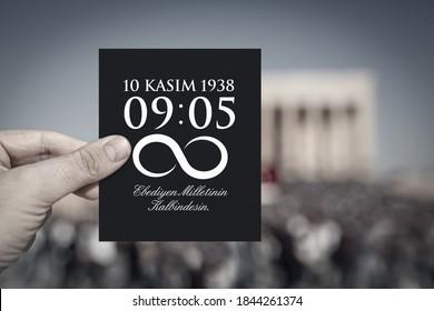 Hand hält ein schwarzes Papier mit der Todesstunde und dem Datum von Atatürk vor dem verschwommenen Anitkabir-Mausoleum im 10. November. Englisch der Botschaft: Sie werden ewig im Herzen Ihrer Nation leben.