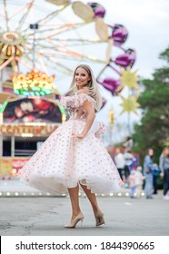 beautiful Russian blonde girl walks in an attraction Park in a fluffy doll dress