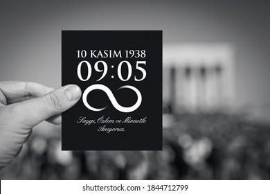 Hand hält Papier mit Todesstunde und Datum von Atatürk vor dem verschwommenen Anitkabir-Mausoleum im 10. November. Englisch der Nachricht: Wir erinnern uns mit Respekt, Sehnsucht und Dankbarkeit an Sie.