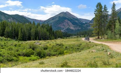 Backcountry Road - Eine abgelegene Forest-Service-Road, die sich an einem sonnigen Sommerabend in der Nähe von Guanella Pass, Grant, Colorado, USA, in einem grünen Tal in Richtung hoher Gipfel der Wasserscheide windet.