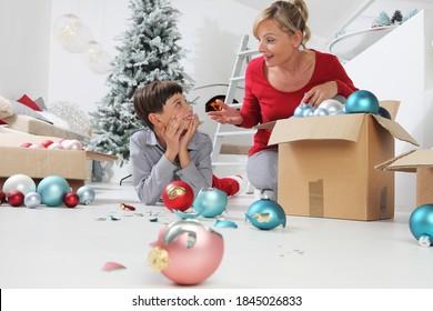 Frohe Weihnachten und schöne Feiertage! Mutter und Sohn schmücken den Weihnachtsbaum im Haus. versehentlich bricht das Kind die Eier, die Mutter schimpft mit ihm