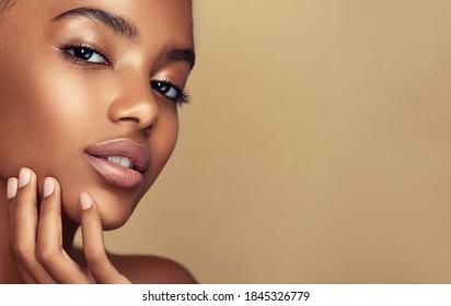 アフリカ系アメリカ人の女の子の美しさの肖像画。美しい黒人女性が彼女の顔に触れます。美顔術 。美容、スキンケア、スパ。