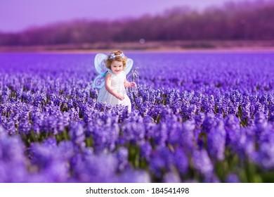 Retrato de una adorable niña pequeña con un disfraz de hada mágica y una corona de flores en su cabello rizado jugando con una varita en un hermoso campo de jacintos morados en Keukenhof, Holanda, en un ventoso día de primavera