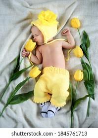 Una niña recién nacida con un traje de punto amarillo está acostada de espaldas entre las flores. Hermoso retrato de un niño pequeño, de una semana de edad.