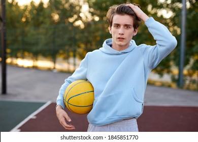 手にボールを持つブルネットのバスケットボール選手の少年の肖像画、白人男性はスポーツゲームを楽しむ、運動後に立つ