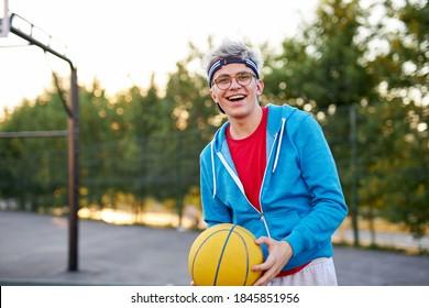 陽気な少年は、屋外の都市の運動場で、素晴らしいバスケットボールの試合、笑いを持っています