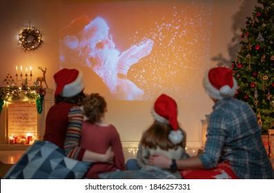 メリークリスマス、そしてハッピーニューイヤー!屋内の木の近くで楽しんでいる人。家で休日の映画を見ている愛する家族。一緒に時間を過ごす母、父、娘。