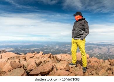 Mann mit Gesichtsbedeckung stehend auf dem Gipfel des Pikes Peak, Colorado. Reisen Sie in Zeiten der Covid-19-Pandemie