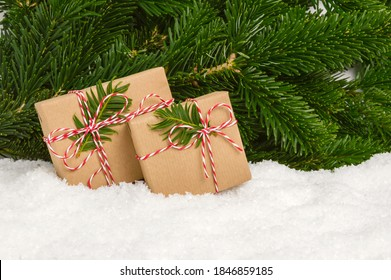 Two handmade plastic-free Christmas presents under fir tree. Gifts wrapped in craft paper and rope bow stand in snow with pine tree branches as background. Winter holiday celebration, giving presents