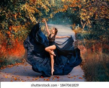 明るい色のアートワーク。道路で踊っている美しい少女バレリーナ。秋の自然の背景。創造的に動いているファッションモデル。長い黒のドレスが風になびく。ファンタジー女性ダンサー