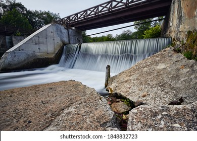 Abandoned small concrete waterfall with a wooden bridge over it and large concrete blocks (rocks) in the front.