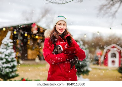 Young attractive woman in red winter overalls and white hat posing with little black pig against Christmas background.Snowing.