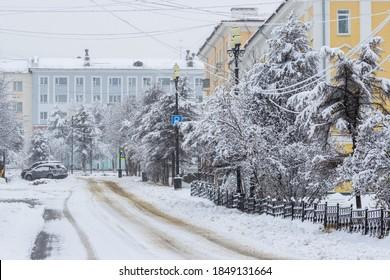 降雪時の空の雪に覆われた街の通りの眺め。雪道。木の枝に新鮮な白い雪。寒い雪の冬の天気。ロシア極東、シベリア、マガダン地域、マガダン市。