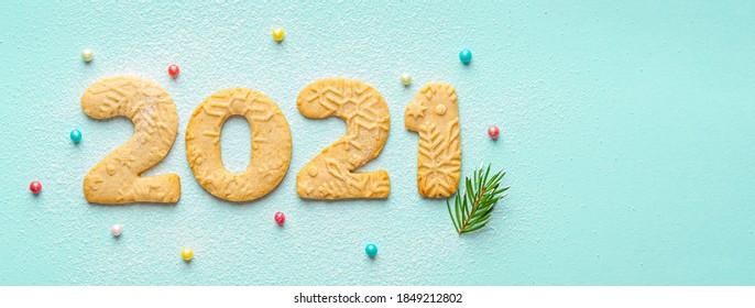 Ziffer 2021 aus Lebkuchen-Weihnachtsplätzchen mit Zuckerpulver. Neujahrskonzept. Nahrungsmittelnummern. 2021 Logo. Kreatives Design. Draufsicht. Münzpapier Hintergrund. Speicherplatz kopieren. Platz für Text.