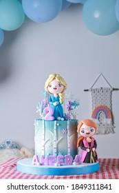 Pastel de cumpleaños de 2 años, tema congelado, fondos de puerta de globos, en la ropa de mesa del cuadrado rojo.