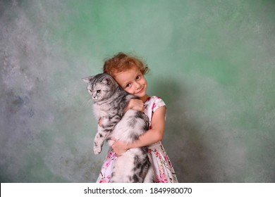 A girl with curly hair, in a beautiful dress with roses, hugs her beloved cat. The girl is standing on a green background.