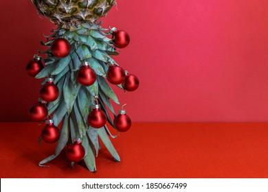 Origineel kerstboomconcept. Rode glanzende glazen kerstballen hangen aan de bladeren van rijpe ananas die ondersteboven staan. Rode achtergrond met kopie ruimte voor uw tekst.