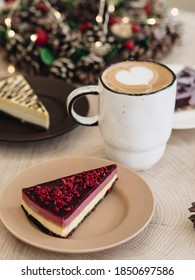 ケーキが皿の上にあります。家の装飾のためのクリスマスリース。中央にはカプチーノコーヒーのマグカップがあります。泡にハートが描かれています。暖かいクリスマスドリンク。クリスのための野菜のお菓子