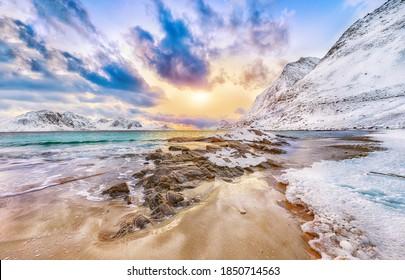 Fantastische Winteransicht des Strandes von Haukland während des Sonnenuntergangs mit viel Schnee und schneebedeckten Berggipfeln nahe Leknes. Ort: Leknes, Vestvagoy, Lofotens, Norwegen