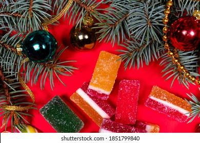 Marmeladni želeji in smrekova vejica s trakom in igračo na rdeči podlagi. Pasica na rdeči podlagi za slaščičarno