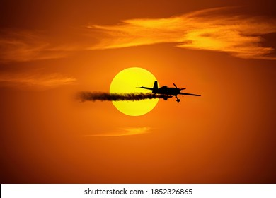 A super lite aircraft on a backdrop of rich orange and yellow tones from the sunset at the end of summer.