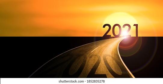 Año nuevo 2021 o comenzar directamente concepto 2020 escrito en la carretera de asfalto al atardecer.