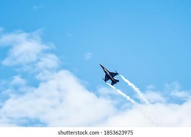 青い空を飛んでいる軍用F16戦闘機。