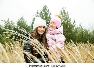 Mutter und Kind gehen im November in Winterkleidung im Freien spazieren.