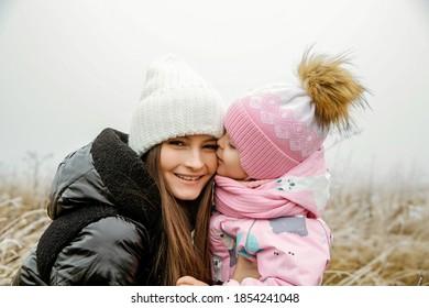 Mutter und Kind Natur Fotosession mit Liebe im November in Winterkleidung gekleidet.
