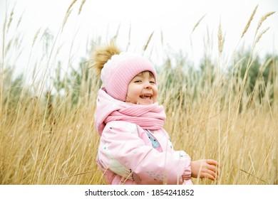 Kind gekleidet in Winterkleidung, die draußen im Weizen lächelt.