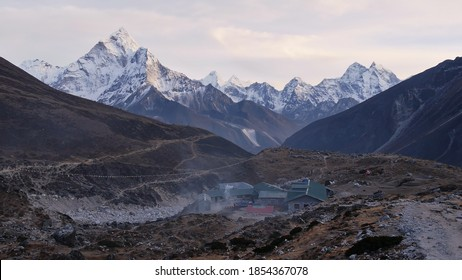 Panoramic view of majestic snow-capped Himalayan mountain range with mighty Ama Dablam (peak: 6,812 m) and Sherpa lodges at Dughla (Thukla) with smoking chimneys in Sagarmatha National Park, Nepal.