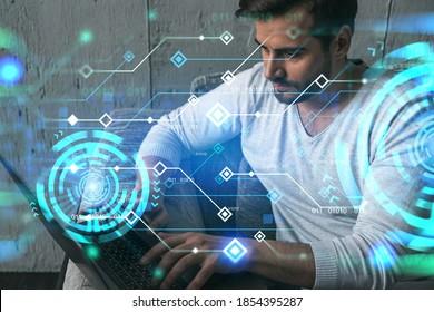 Ein ernsthafter kaukasischer Mann in Freizeitkleidung, der einen Laptop eingibt, um einen neuen Entwicklercode für die App zu erstellen. Doppelbelichtung. Informationslinks Hologramm.