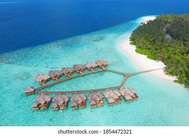 Kleine Insel auf den Malediven, bedeckt von Palmen und umgeben von türkisblauem Wasser mit wunderschönen Korallen und Tieren, perfekte Flucht aus dem kalten Winter