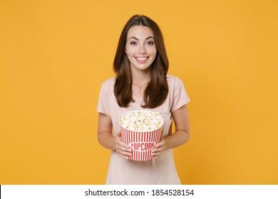 パステルピンクのカジュアルなTシャツを着て笑顔の若いブルネットの女性が明るい黄色の壁の背景スタジオの肖像画に分離されたポップコーン探しカメラのバケツを保持している映画フィルムを見てポーズ