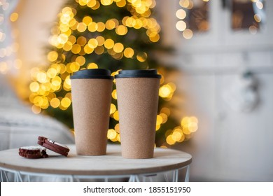 Coffee to go is on the table in the cafe.  Christmas mood is a warm beverage.  Mulled wine tea winter take away drink.  Reusable zero waste mug.  Two friends couple concept. New year Bokeh background