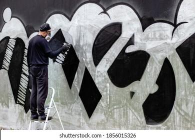 はしごの上に立って、フィルター付きの保護フェイスマスク/レスピレーターを着用しているグラフィティアーティスト。壁の缶にスプレーペイントで抽象画。ストリートアート文化のコンセプト。