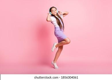 Foto in voller Länge von positivem kleinen Kindermädchen hören drahtlose Headset-Musik lokalisiert über rosa Farbhintergrund