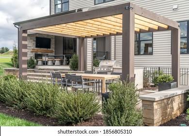 Estructura de sombra de pérgola de patio al aire libre de moda, toldo y techo de patio, mesa de comedor, sillas, parrilla de metal rodeada de jardines