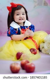 Asiatisches Baby in einem Märchenkostüm, Schneewittchen, mit Äpfeln und Blumen