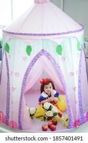 Asiatisches Baby in einem Märchenkostüm, Schneewittchen, mit Äpfeln und Blumen in einem Schlosszelt
