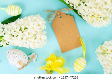 Osterszene mit Frühlingsblumen und farbigen Eiern, flacher Laderahmen auf blauem Hintergrund, Kopierraum auf Papiernotiz