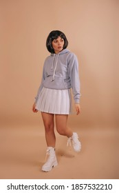 Hot girl with a bob haircut, in a hoodie and a white short skirt walking isolated beige background. Anime fan.
