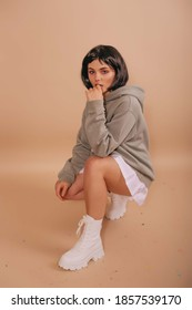 Hot girl with a bob haircut, in a hoodie and a white short skirt sitting isolated beige background. Anime fan.