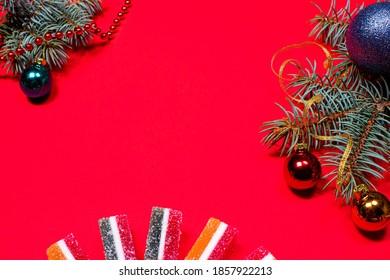 Marmeladni želeji in smrekova vejica s trakom in igračo na rdeči podlagi. Pasica na rdeči podlagi s prostorom za besedilo v copyspaceu.